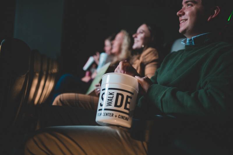 The same four members are still seated in the theater, but the focus is on a bucket of popcorn.